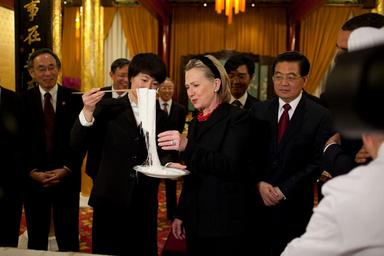 HIlary clinton is presented with an unfamiliar Japanese dish at a political function.